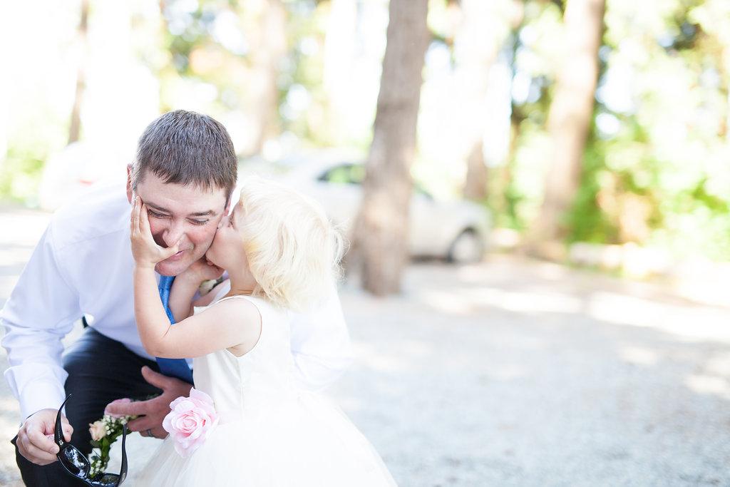 flower girl kissing groom